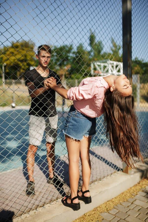 Situación hermosa joven de los pares entre la cerca de la malla y las manos el sostenerse otra en la cancha de básquet imagenes de archivo