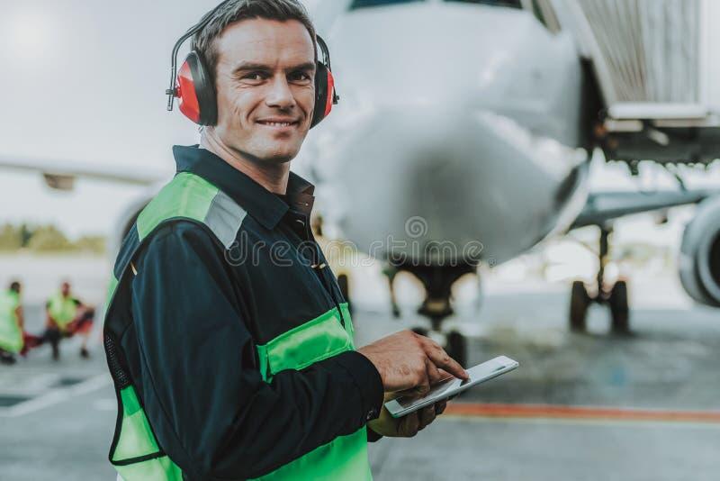 Situación hermosa sonriente del trabajador delante del avión enorme imagen de archivo