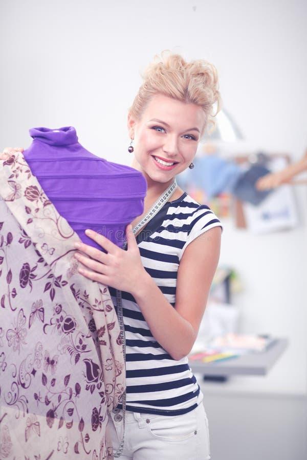 Situación joven de la mujer del diseñador de la moda cerca del maniquí imagen de archivo libre de regalías