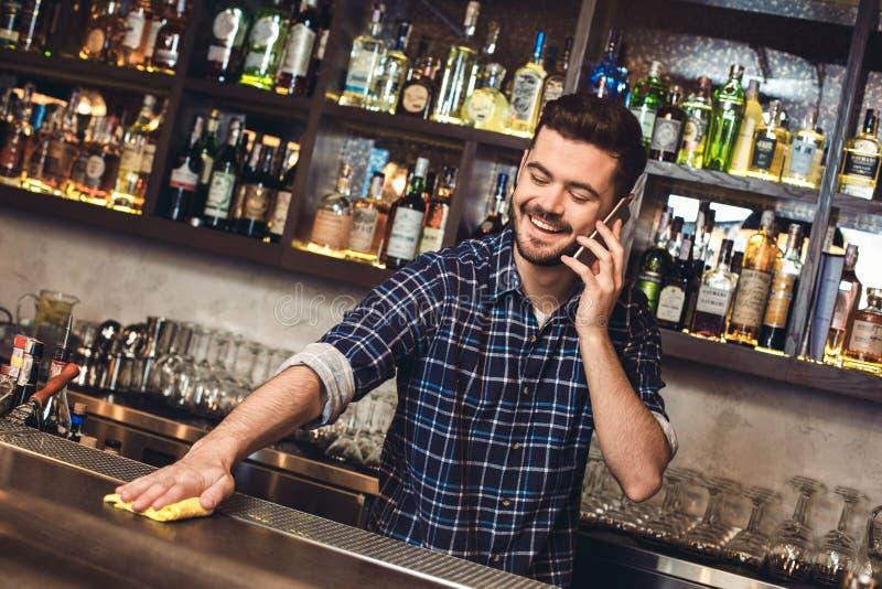 Situación joven del camarero en el contador de la barra que habla en la tabla de limpieza del smartphone alegre fotografía de archivo