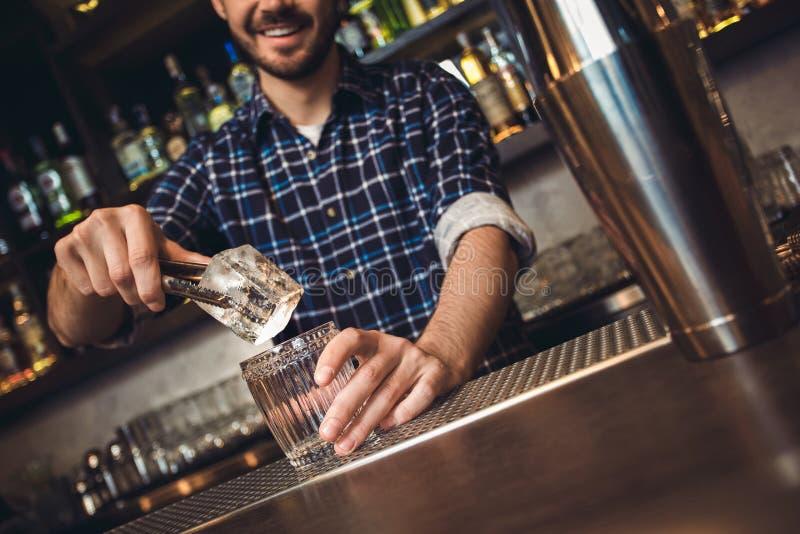 Situación joven del camarero en el contador de la barra que pone el cubo de hielo en alegre de cristal imágenes de archivo libres de regalías