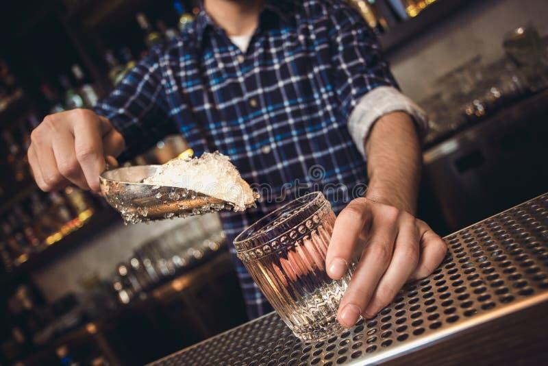 Situación joven del camarero en el contador de la barra que pone el hielo afeitado en el primer de cristal foto de archivo