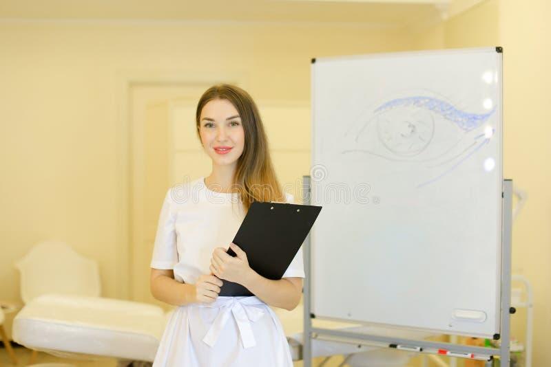 Situación joven del cosmetologist con la carpeta negra cerca del cartel con el ojo exhausto en el gabinete de la cosmetología fotografía de archivo libre de regalías