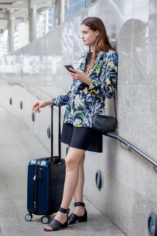 situación joven feliz de la mujer de negocios con bulto de mano usando el teléfono móvil muchacha que viaja con la maleta y smart fotos de archivo libres de regalías
