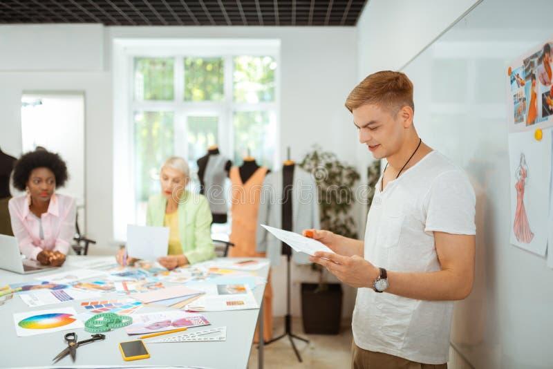 Situación masculina del diseñador de moda en una tabla que corta fotografía de archivo libre de regalías