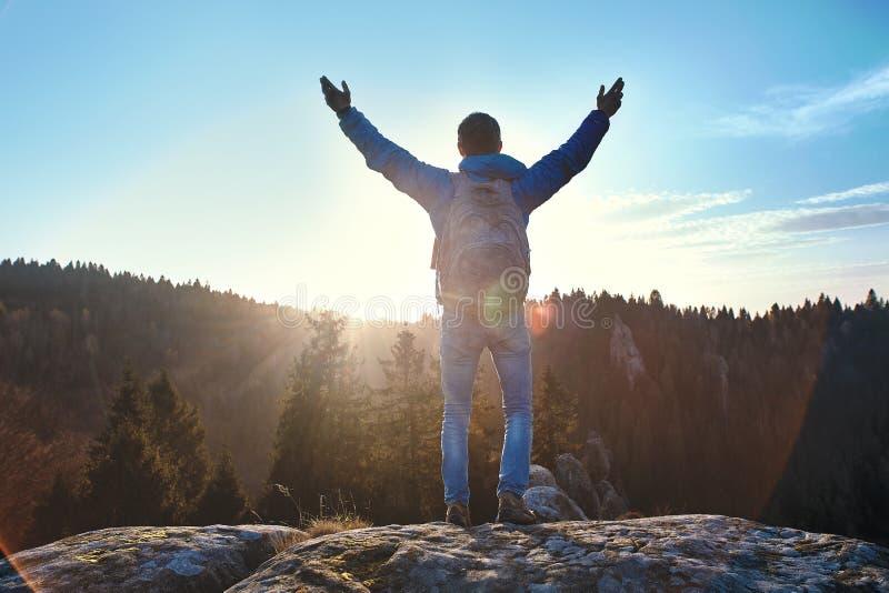 Situación masculina del viajero en el acantilado contra las colinas enselvadas y el cielo nublado en la salida del sol El hombre  fotografía de archivo libre de regalías