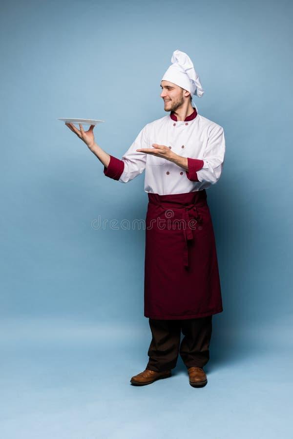 Situación masculina feliz del cocinero del cocinero con la placa aislada en fondo azul claro imágenes de archivo libres de regalías