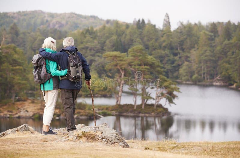Situación mayor de los pares que abraza y que admira la vista de un lago, visión trasera fotografía de archivo