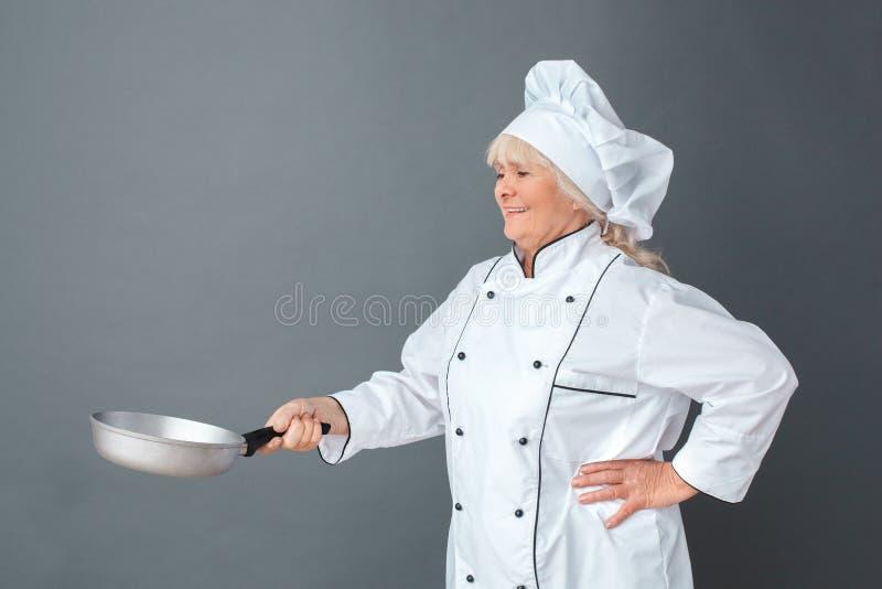 Situación mayor del estudio del cocinero de la mujer aislada en gris con vista lateral alegre del sartén fotos de archivo libres de regalías