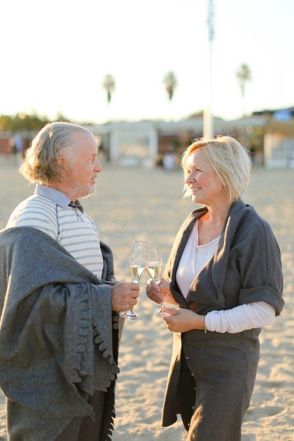 Situación mayor del marido y de la esposa con los vidrios del champán en la playa de la arena imágenes de archivo libres de regalías