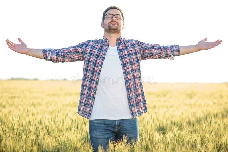Situación milenaria joven orgullosa del granjero en campo de trigo con los brazos extendidos fotografía de archivo
