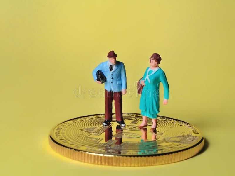 Situación miniatura de la gente en las monedas que disfrutan de renta o ganar fotografía de archivo libre de regalías