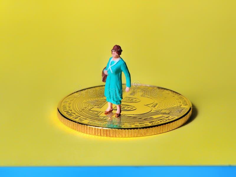 Situación miniatura de la gente en las monedas que disfrutan de renta o ganar fotos de archivo libres de regalías