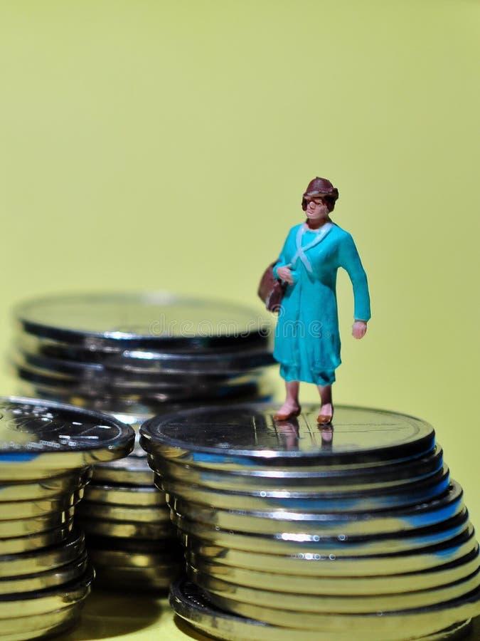 Situación miniatura de la gente en las monedas que disfrutan de renta o ganar foto de archivo libre de regalías
