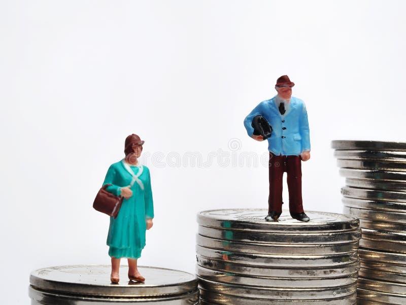 Situación miniatura de la gente en la pila de monedas con diversa altura foto de archivo