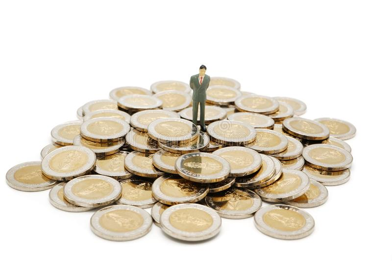 Situación miniatura de la gente en la pila de nuevas 10 monedas del baht tailandés imagenes de archivo