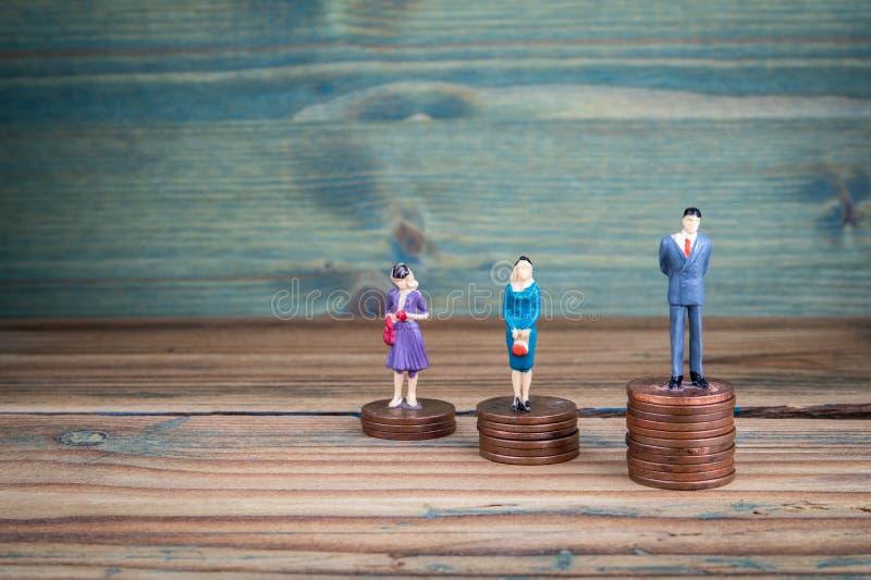 Situación miniatura de la gente en pilas de monedas imagen de archivo libre de regalías