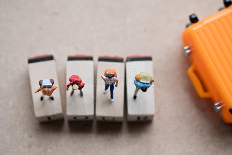 Situación miniatura de la mochila del viajero y del caminante del grupo en etiqueta de madera con la maleta imágenes de archivo libres de regalías