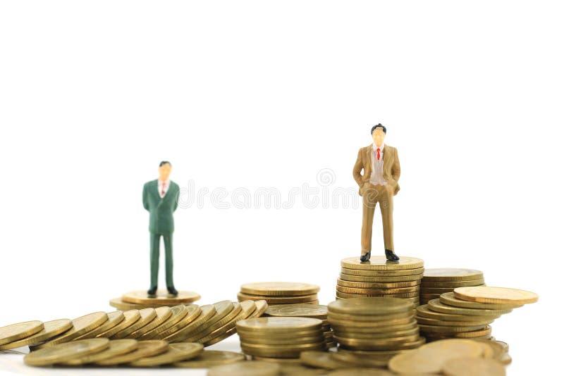 Situación miniatura del hombre de negocios en la pila de dinero de las monedas en el concepto financiero blanco del fondo, de la  foto de archivo libre de regalías