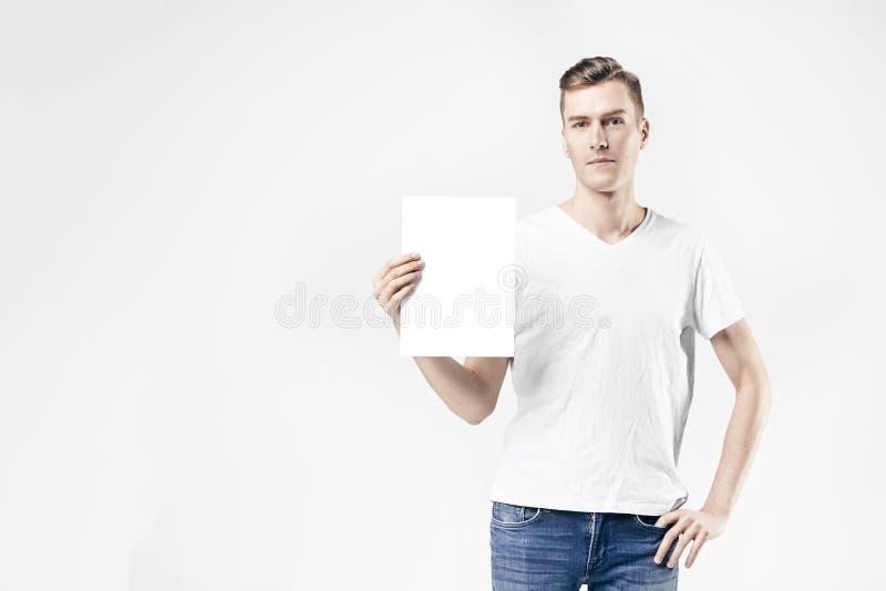 Situación modelo del hombre del inconformista con la hoja en blanco en las manos, aisladas en el fondo blanco, vaqueros que lleva fotos de archivo
