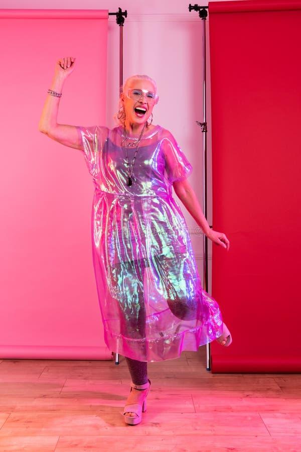 Situación modelo mayor encantada positivo sobre rosa fotos de archivo