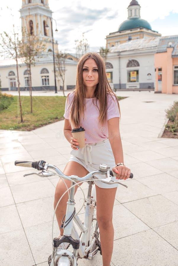 Situación morena de la mujer de la muchacha hermosa en parque en la bici En el verano en la ciudad, en su mano una taza de café o imagenes de archivo