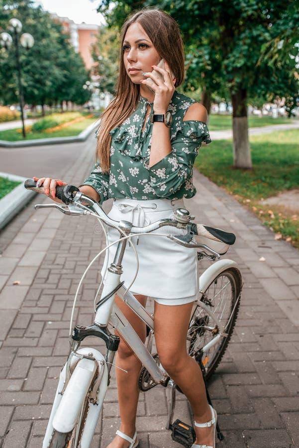 Situación morena de la mujer de la muchacha hermosa en parque en una bicicleta Llamadas por el teléfono en el verano en la ciudad fotos de archivo libres de regalías