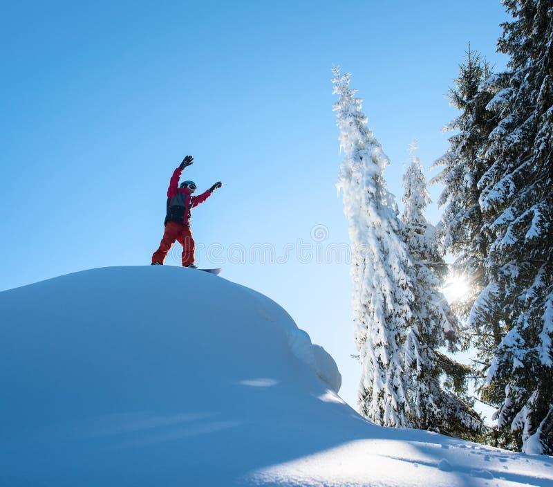 Situación parasitario del Snowboarder encima de la cuesta del esquí con sus brazos en el aire en gesto victorioso en las montañas imagenes de archivo