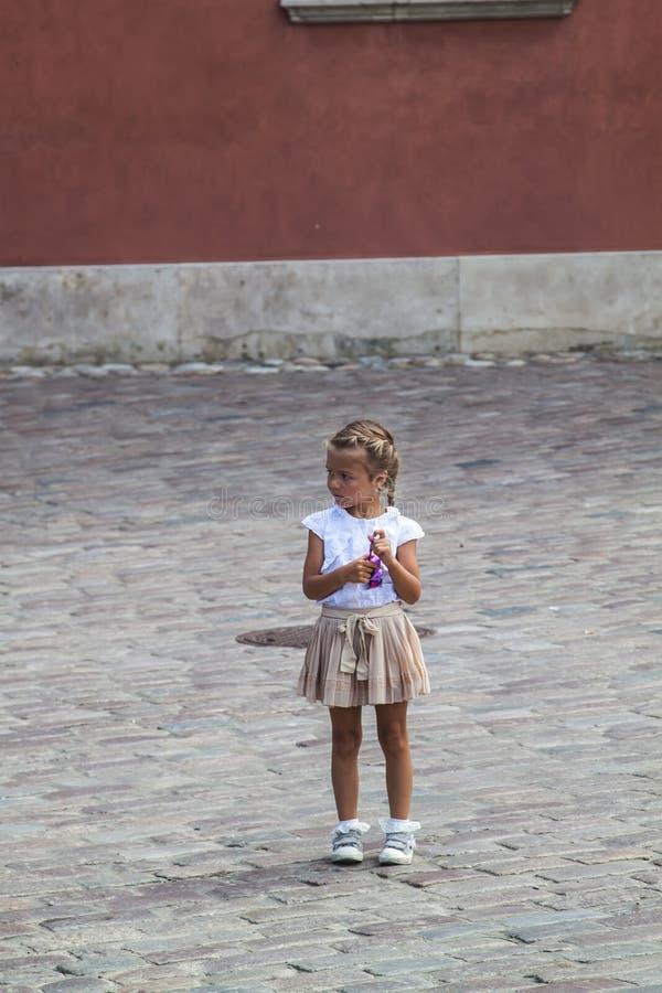 situación pensativa de la niña sola en el pavimento en el cuadrado imagenes de archivo