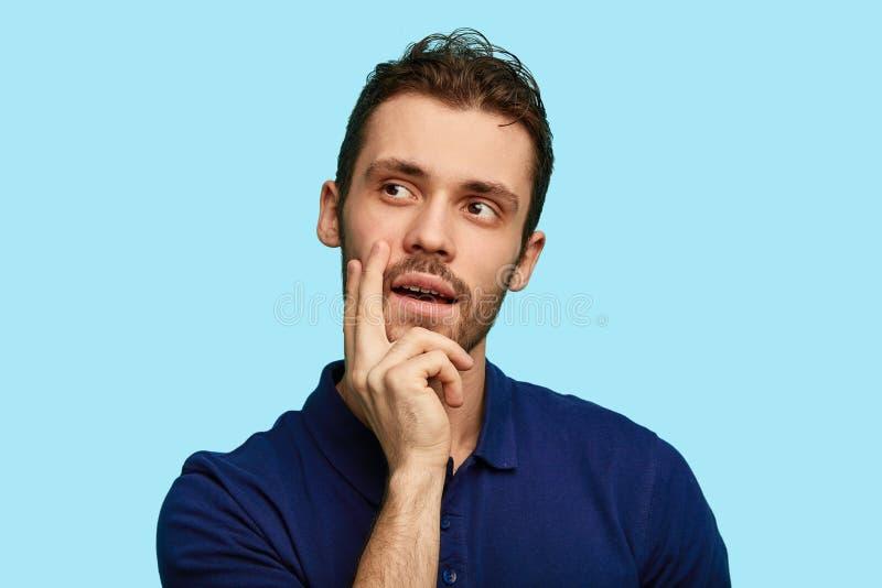 Situaci?n pensativa del hombre con la mano en la barbilla y la mirada de ausente aislada sobre fondo azul fotografía de archivo libre de regalías