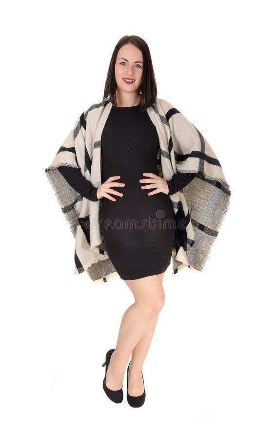 Situación preciosa de la mujer joven en vestido negro con un poncho imagen de archivo libre de regalías
