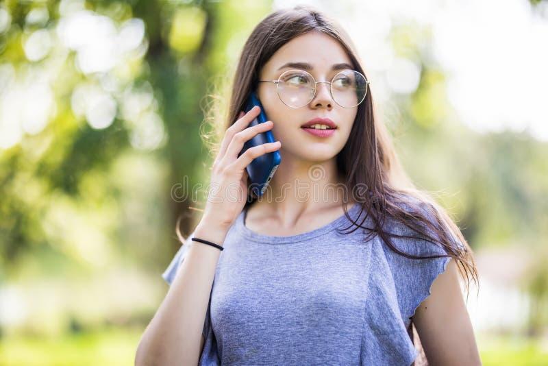 Situación preciosa feliz de la mujer joven y el hablar en el teléfono celular en parque fotos de archivo
