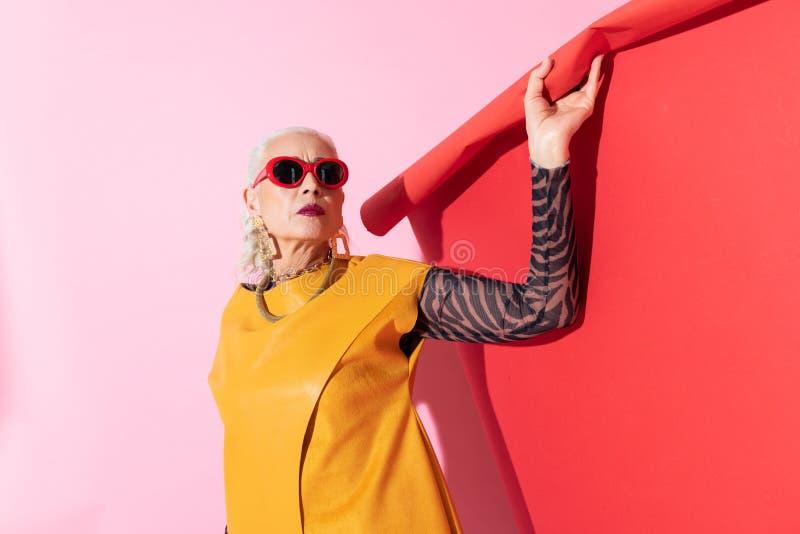 Situación rubia atractiva de la mujer sobre fondo rosado fotografía de archivo
