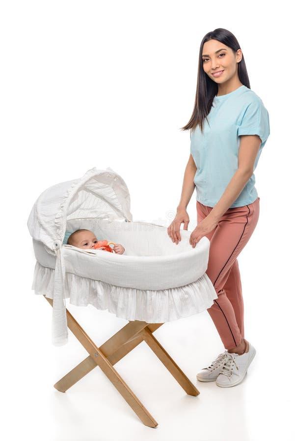 situación sonriente de la mujer cerca del pesebre con el bebé infantil fotografía de archivo libre de regalías