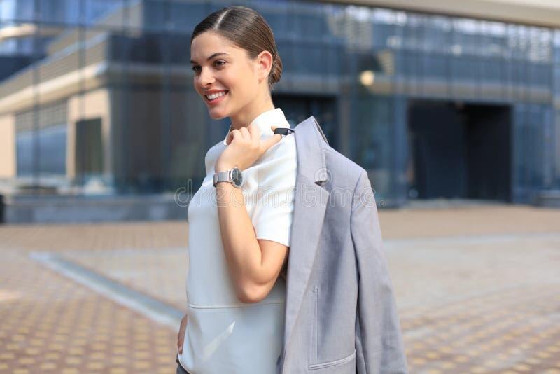 Situación sonriente de la mujer de negocios con una chaqueta sobre su hombro cerca del edificio de oficinas imagen de archivo