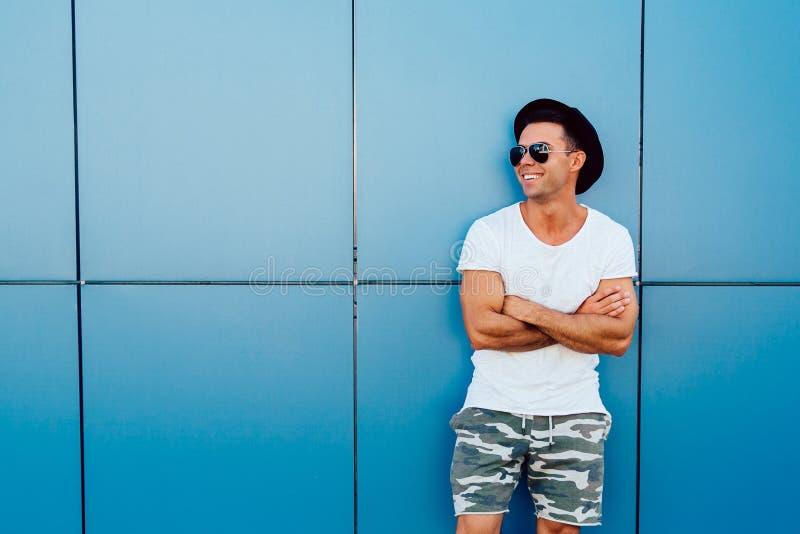 Situación sonriente del hombre en fondo azul de la pared al aire libre imágenes de archivo libres de regalías