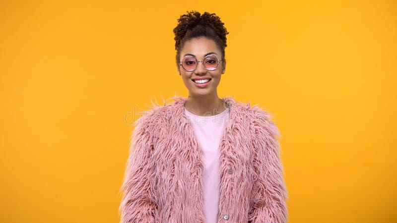 Situación sonriente femenina elegante atractiva en el fondo amarillo, buen humor imágenes de archivo libres de regalías