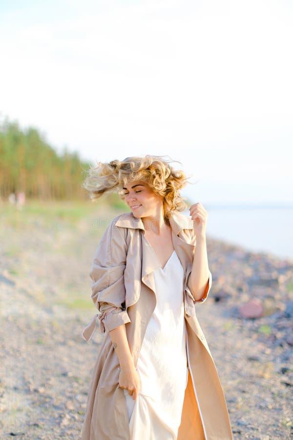 Situación sonriente joven de la muchacha en la playa del mar y la capa que lleva con el vestido blanco foto de archivo