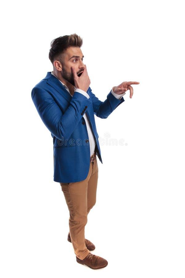 Situación sorprendente del hombre con la mano en la boca y el finger el señalar imagen de archivo