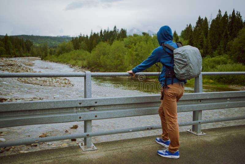situación turística masculina al lado del río de la montaña fotos de archivo