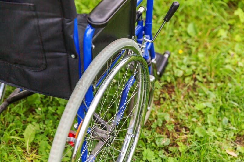 Situación vacía de la silla de ruedas en hierba en servicios pacientes que esperan del parque del hospital para fotografía de archivo libre de regalías