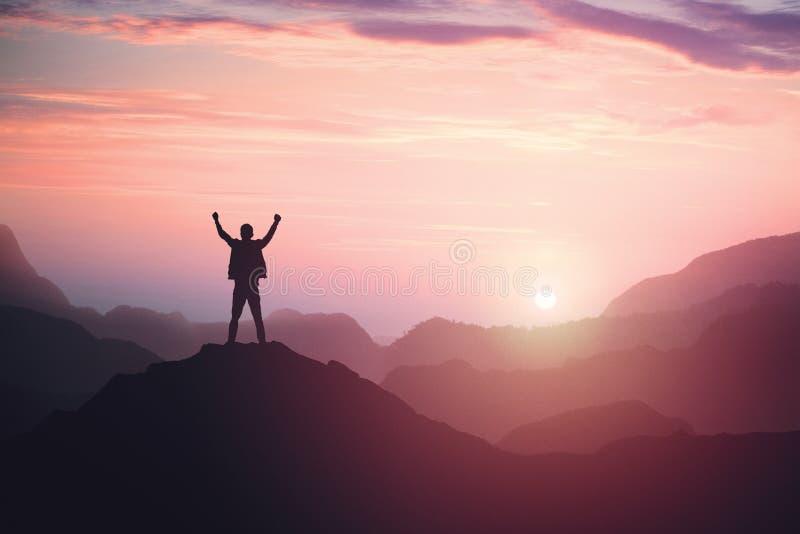 Situación victoriosa de la persona masculina en el top de la montaña con los brazos aumentados El ganar y ?xito imagen de archivo libre de regalías