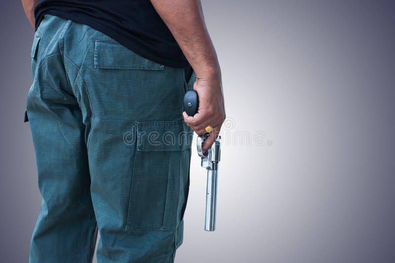 Situación y mano del hombre que llevan a cabo el revólver del arma foto de archivo