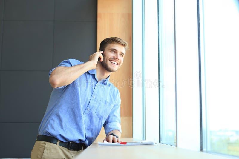 Situación y usar sonrientes del hombre de negocios el teléfono móvil en oficina fotos de archivo