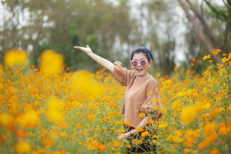 Situaci?n asi?tica sonriente de la mujer de la cara del retrato con la emoci?n de la felicidad en campo floreciente del cosmos am fotos de archivo libres de regalías