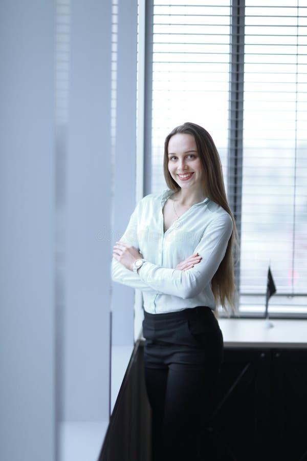 Situaci?n de la mujer de negocios cerca de la ventana en el pasillo de la oficina imagen de archivo