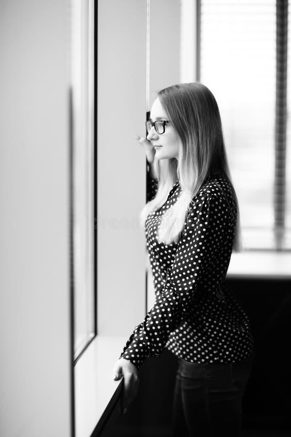 Situaci?n de la mujer de negocios cerca de la ventana en oficina fotografía de archivo
