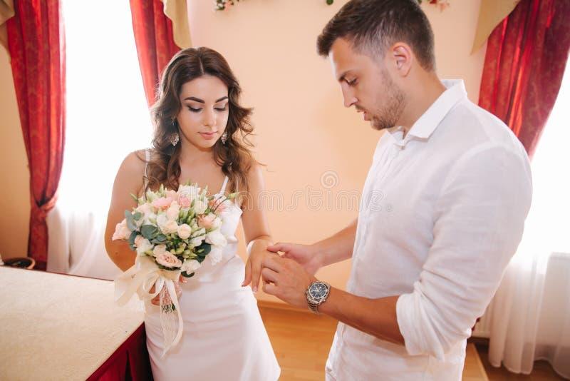 Situaci?n del novio y de la novia dentro de la casa del matrimonio Pares hermosos en blanco fotos de archivo
