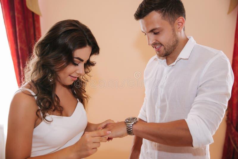 Situaci?n del novio y de la novia dentro de la casa del matrimonio Pares hermosos en blanco imagen de archivo libre de regalías