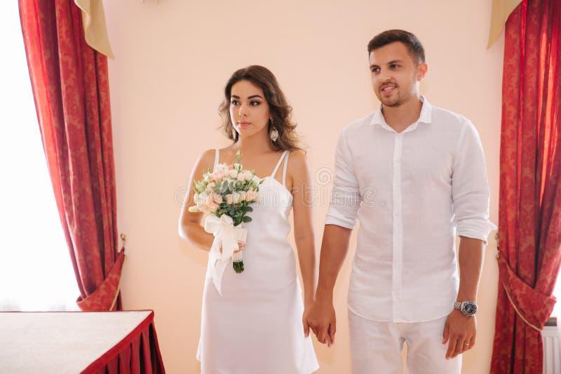 Situaci?n del novio y de la novia dentro de la casa del matrimonio Pares hermosos en blanco fotos de archivo libres de regalías